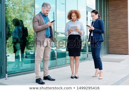 Group of young contemporary mobile employees in formalwear using gadgets Stock photo © pressmaster