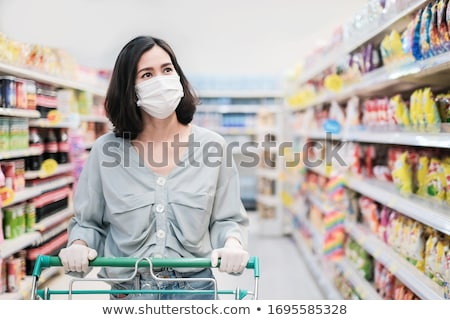 Beautiful young woman shopping for grocery products at a grocery store supermarket Stock photo © galitskaya