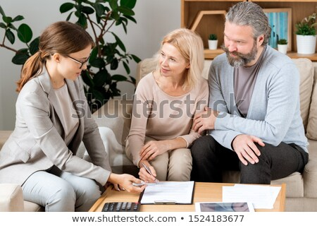 Zdjęcia stock: Mature Blonde Woman Listening To Real Estate Agent While Going To Sign Contract