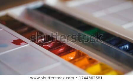 Painter holding palette with mixed colors and putting paintbrush in water Stock photo © pressmaster
