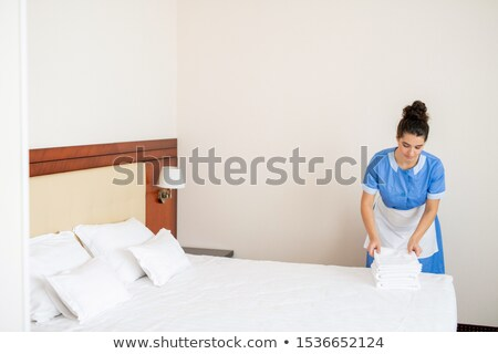 Young chamber maid in uniform making stack of fresh soft towels on edge of bed Stock photo © pressmaster