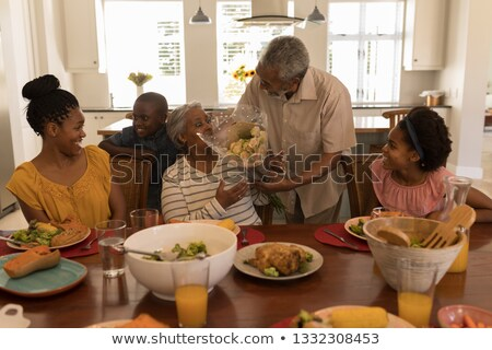 front view of african american senior man giving a beautiful flower bouquet to his wife surrounded stock photo © wavebreak_media