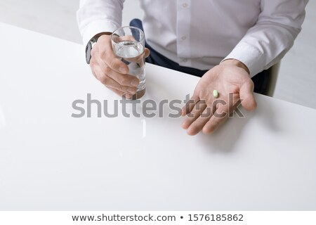 Hands of businessman holding pill while going to take it and glass of water Stock photo © pressmaster