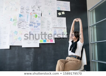 Young tired businesswoman stretching arms while sitting on chair by blackboard Stock photo © pressmaster