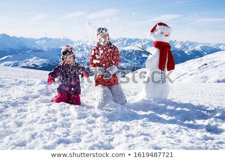 Fille mère jouer neige bonhomme de neige joli Photo stock © AndreyPopov