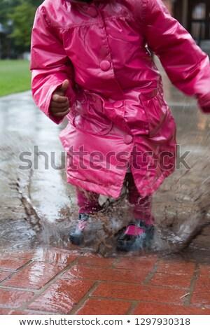 Derűs kicsi lány szórakozás pocsolya utca Stock fotó © dashapetrenko