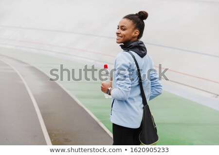 Smiling fit young african sportswoman carrying sportsbag Stock photo © deandrobot