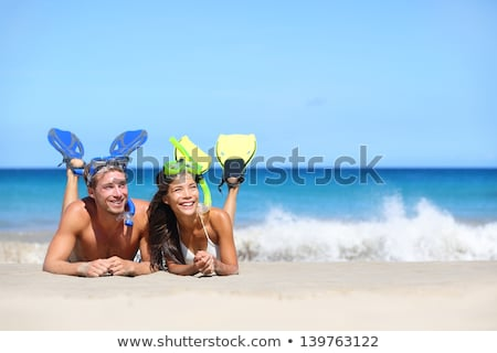 Beach travel people having fun snorkeling. Happy young interracial couple on beach with snorkel mask Stock photo © Maridav