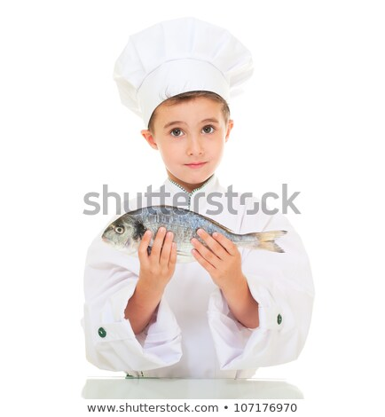 Stock photo: Little boy chef in uniform presenting dorado fish