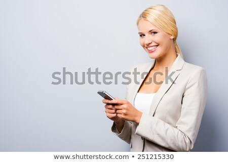 Stock photo: Good looking woman on the phone while standing against a white background