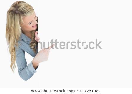 Glimlachende vrouw wijzend poster verbergen achter hand Stockfoto © wavebreak_media