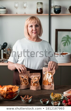 Portrait of happy woman holding cookie and fruit bowl stock photo © wavebreak_media