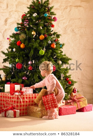 Little girl with parcels round Christmas tree Stock photo © monkey_business