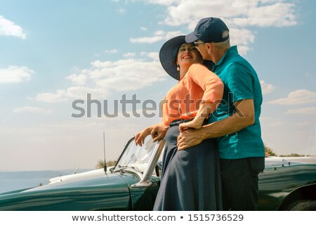Stock photo: Man and woman relaxing near the ocean at sunset