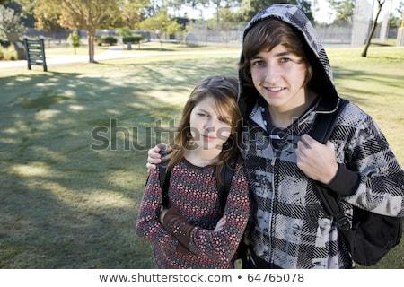 Feliz irmãos irmã em pé brasão em torno de Foto stock © wavebreak_media