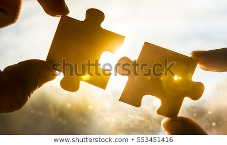 Stock photo: hands trying to link two pieces of a puzzle