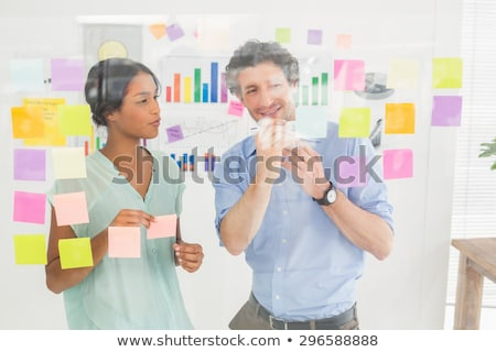 Concentrated businesswoman looking post its on the wall Stock photo © wavebreak_media