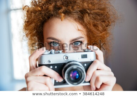 attractive redhead woman photographer using old camera stock photo © deandrobot