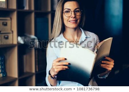 Portrait of a smart beautiful woman holding magazine Stock photo © deandrobot