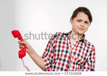 Displeased Girl in shirt holding handset Stock photo © deandrobot