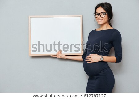 happy pregnant business lady holding copyspace blank stock photo © deandrobot