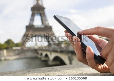 Stock photo: Woman on phone in front of Eiffel tower