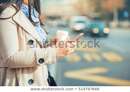 attractive young woman using mobile phone on street stock photo © boggy