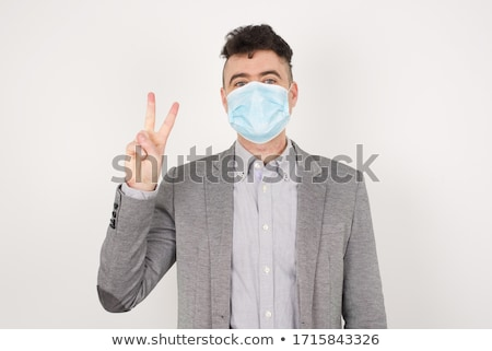 Portrait of a happy cheerful man pointing two fingers up Stock photo © deandrobot