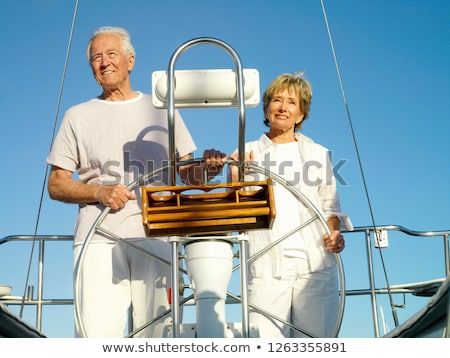 Mature couple at wheel of yacht smiling Stock photo © IS2