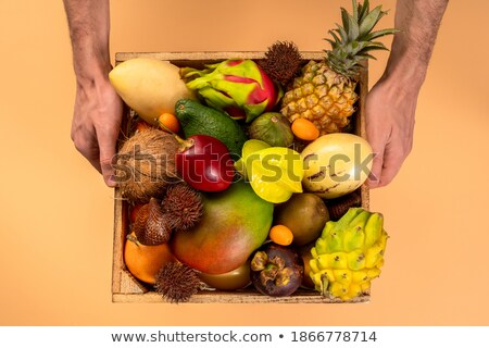 The box with exotic tropical fruits - fresh ripe pineapple, mango, dragon fruit, orange, carambola,  Stock photo © artjazz