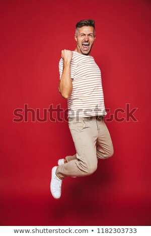 Cheerful man 30s in striped t-shirt screaming and clenching fist Stock photo © deandrobot