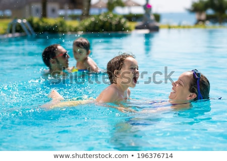 young mother teach her little son how to swim in a swimming pool stock photo © galitskaya