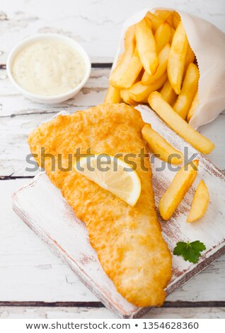 Traditional British Fish and Chips with tartar sauce on chopping board on white woode background.  stock photo © DenisMArt