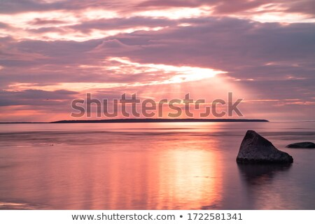 Sunset landscape with golden sun and stones at sea Stock photo © vapi