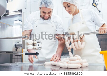 Butcher man and woman working together mincing meat Stock photo © Kzenon