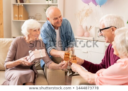 Cheerful friendly seniors clinking with flutes of champagne Stock photo © pressmaster