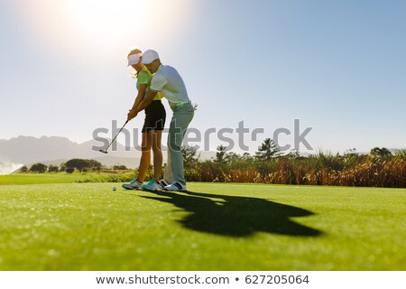 Male trainer teaching the couple to play golf Stock photo © Kzenon