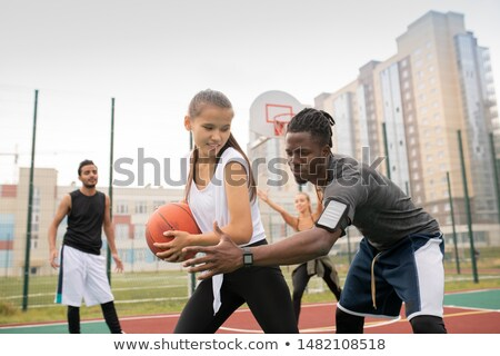 African basketballer keeping his hand by ball held by female player Stock photo © pressmaster