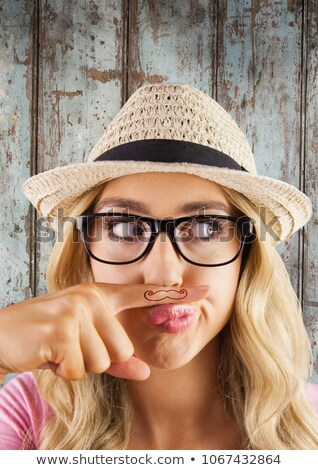 Millennial woman with mustache on finger against wood panel Stock photo © wavebreak_media