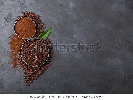 Fresh raw organic coffee beans with ground powder and coffee trea leaf on black background. stock photo © DenisMArt
