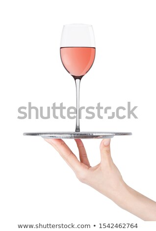 Hand holds tray with pink rose wine glass on white Stock photo © DenisMArt