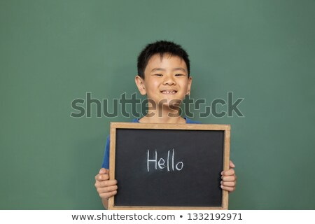 Front view of smiling Asian schoolboy standing and holding a hello slate in a classroom at elementar Stock photo © wavebreak_media