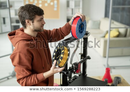 Young creative man changing spool with filament while standing by 3d printer Stock photo © pressmaster