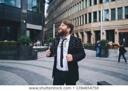 Positive young unshaven male entrepreneur has pleasant smile, dressed in elegant clothes, rejoices s Stock photo © vkstudio