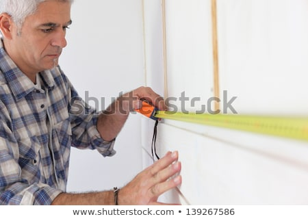 Grey-haired man measuring wall Stock photo © photography33