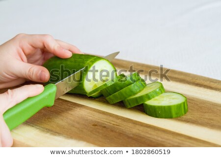 cutting cucumber with a kitchen knife stock photo © bdspn