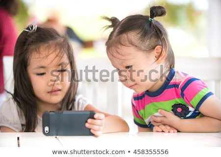 Little Girl In Grass Playing With Cell Phone stock photo © feverpitch