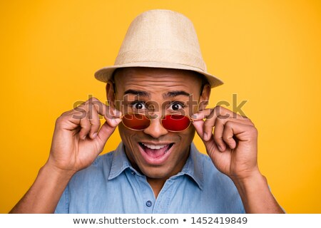 amazing young african man wearing glasses and hat stock photo © deandrobot