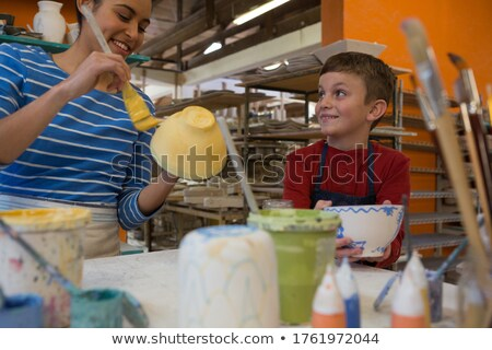 Female potter interacting with boy while painting bowl Stock photo © wavebreak_media