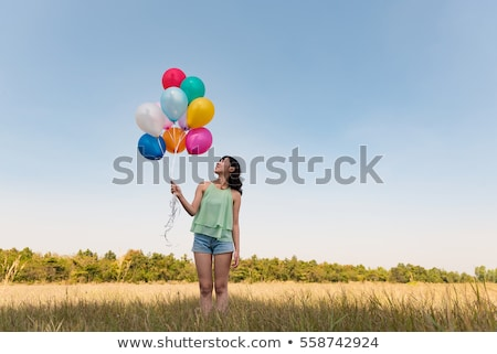 asian woman holding balloons stock photo © LightFieldStudios